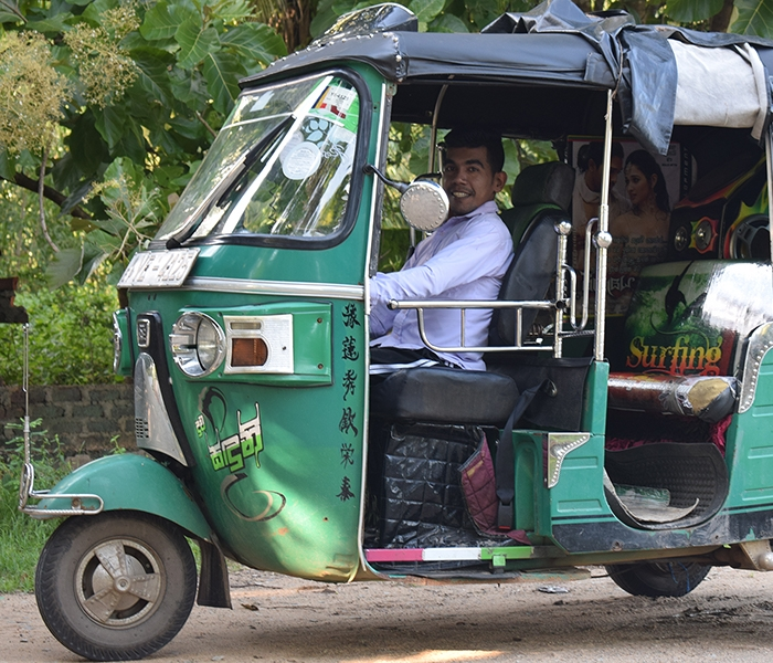 A person driving a modified three-wheeler vehicle