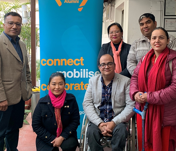 Six people posing and standing or sitting in a wheelchair in front of an Australia Awards banner
