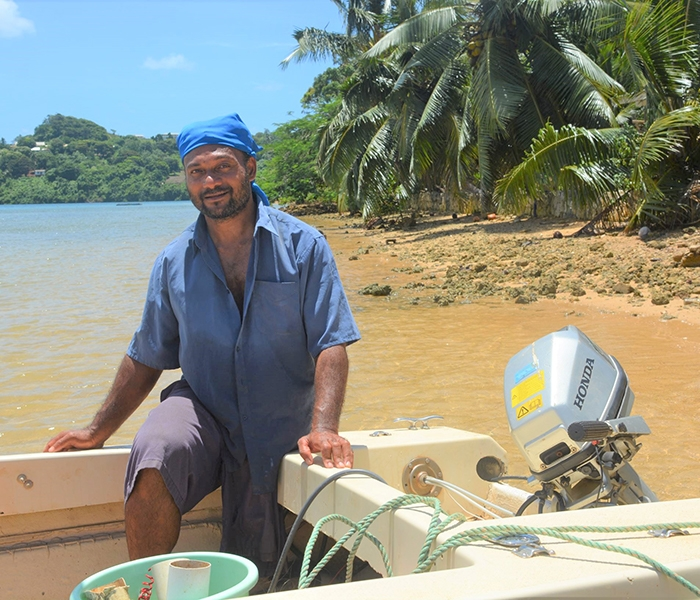 A person sitting in their boat with their repaired outboard motor. They are in a tropical beach location