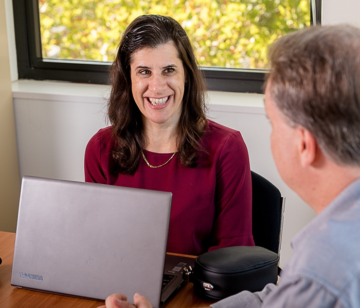 A person with a laptop smiling and talking with another person